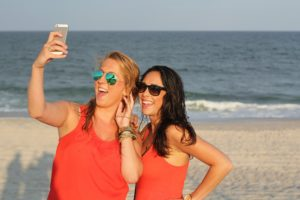 Beach buds wear same top for seaside selfies but sport their own unique sunglass styles.